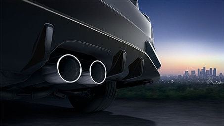 Zoomed-in view of the back of a grey Honda with exhaust pipes in focus.