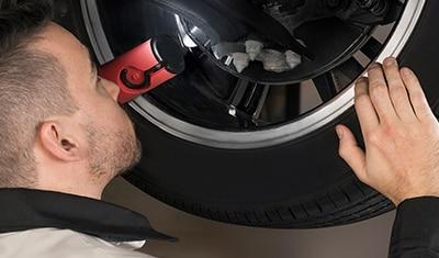 Gros plan d'un technicien certifié Honda inspectant la roue d'un véhicule.