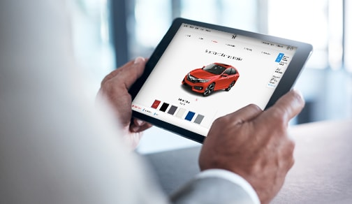Person holding a tablet, visiting the Honda website