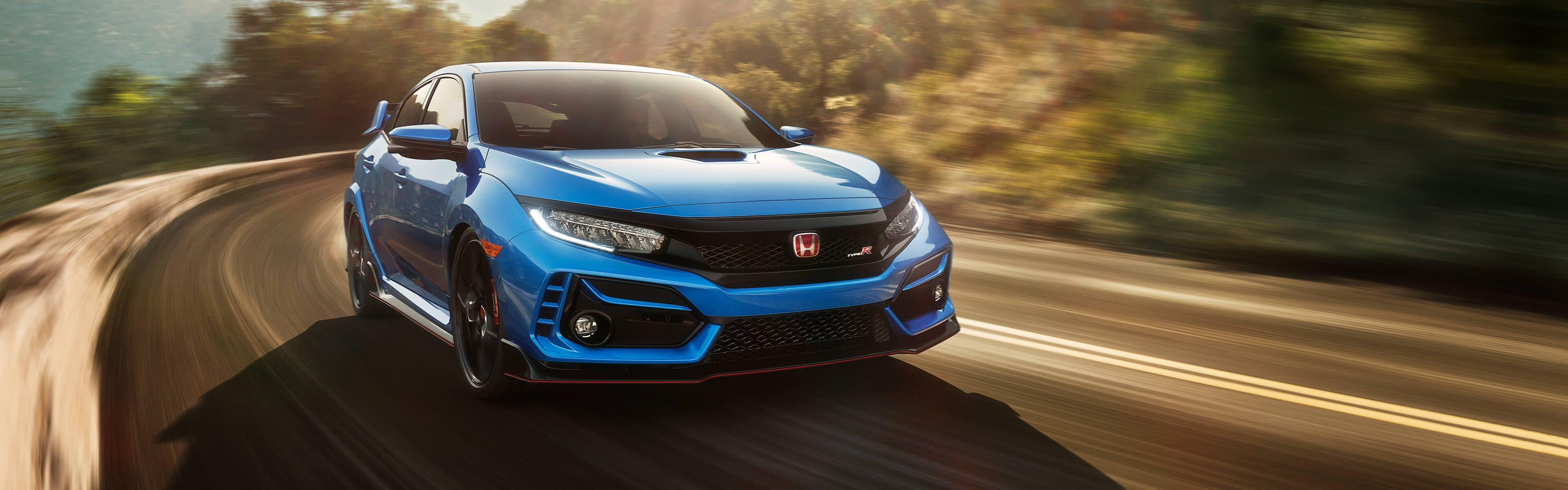 Front passenger-side view of the 2020 Honda Civic Type R Touring in Boost Blue Pearl, driving on a mountain road.