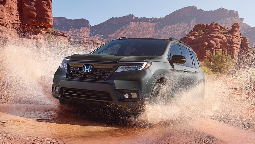 Front 3/4 view of 2019 Honda Passport Touring in Modern Steel Metallic making a splash on a muddy dirt road.