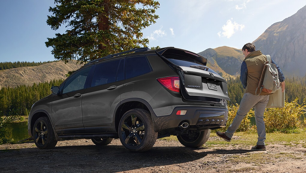 Rear 3/4 view of 2019 Honda Passport being opened via the available hands-free power tailgate.