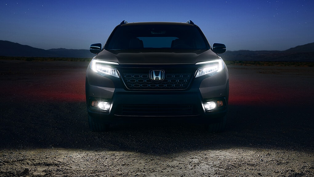 Front view of 2019 Honda Passport with active LED headlights at dusk.
