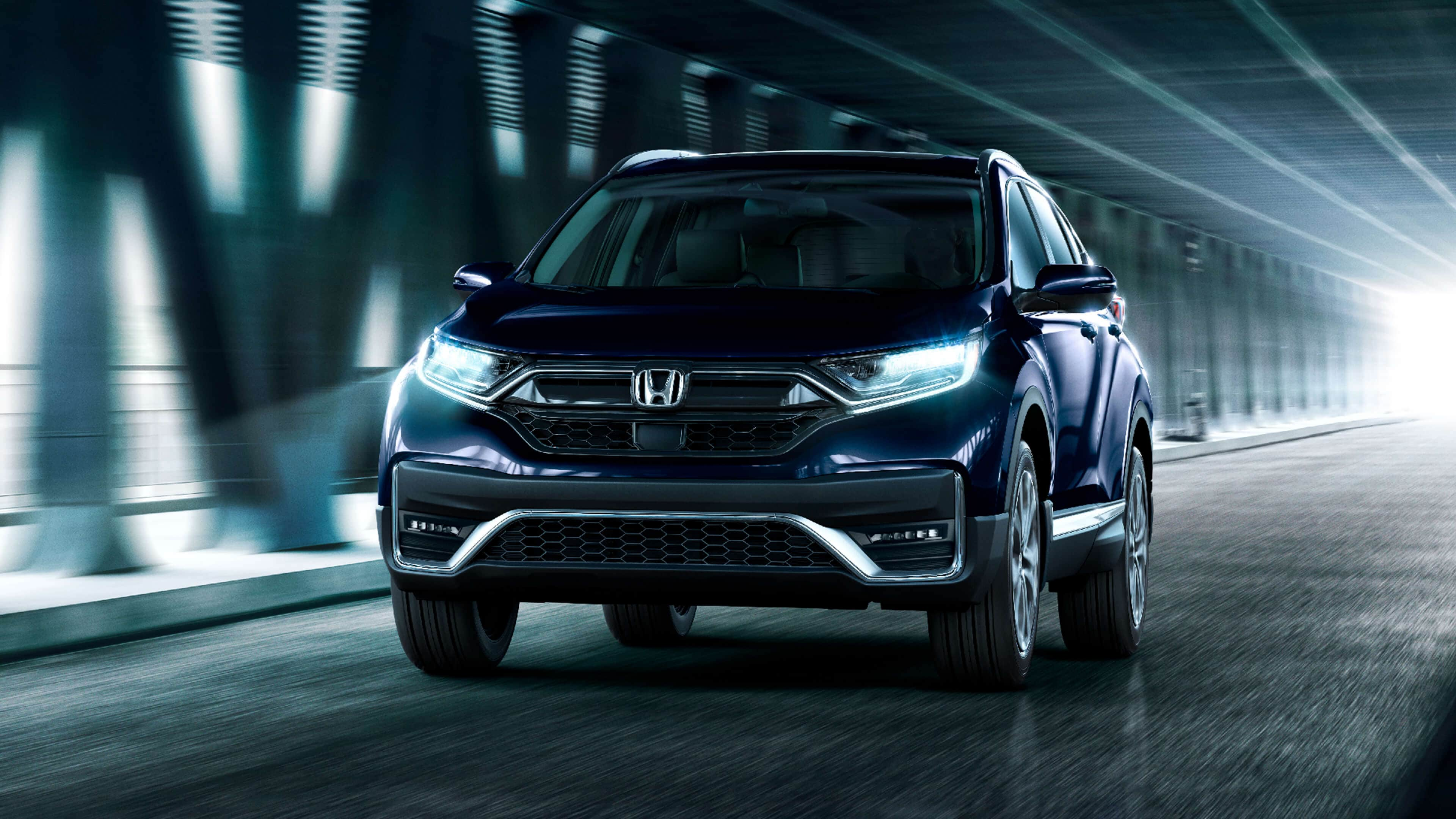 Front view of the 2021 Honda CR-V Touring in Obsidian Blue Pearl, driving under an urban overpass.