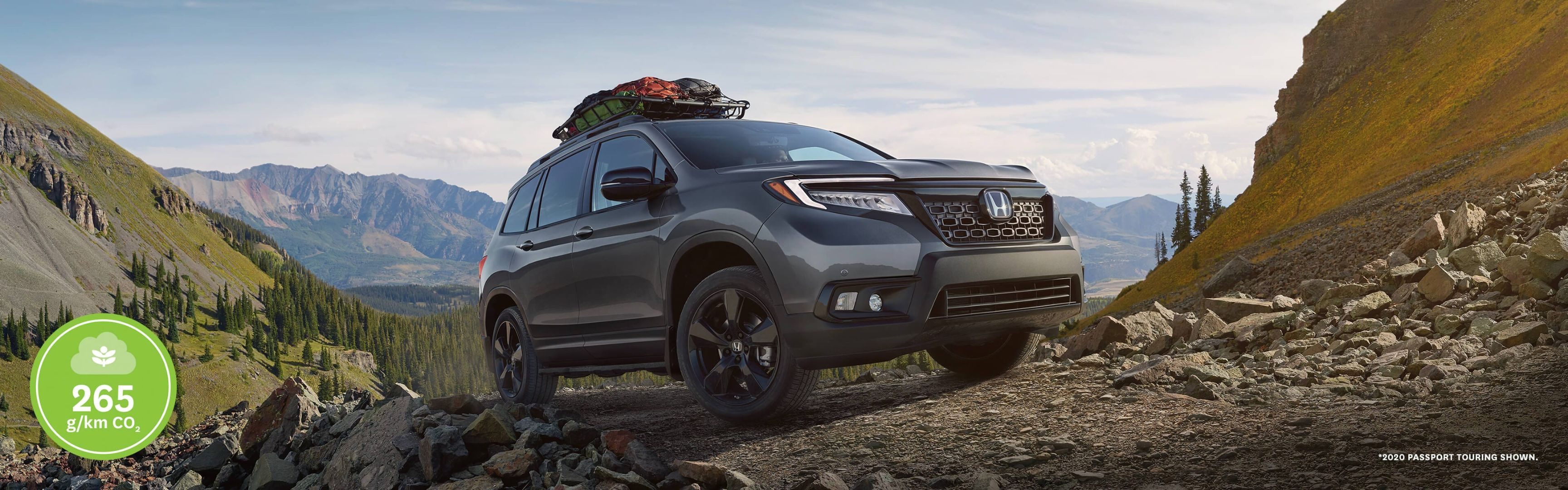 Front 3/4 view of 2020 Honda Passport Touring in Modern Steel Metallic parked at a campsite next to a lake.